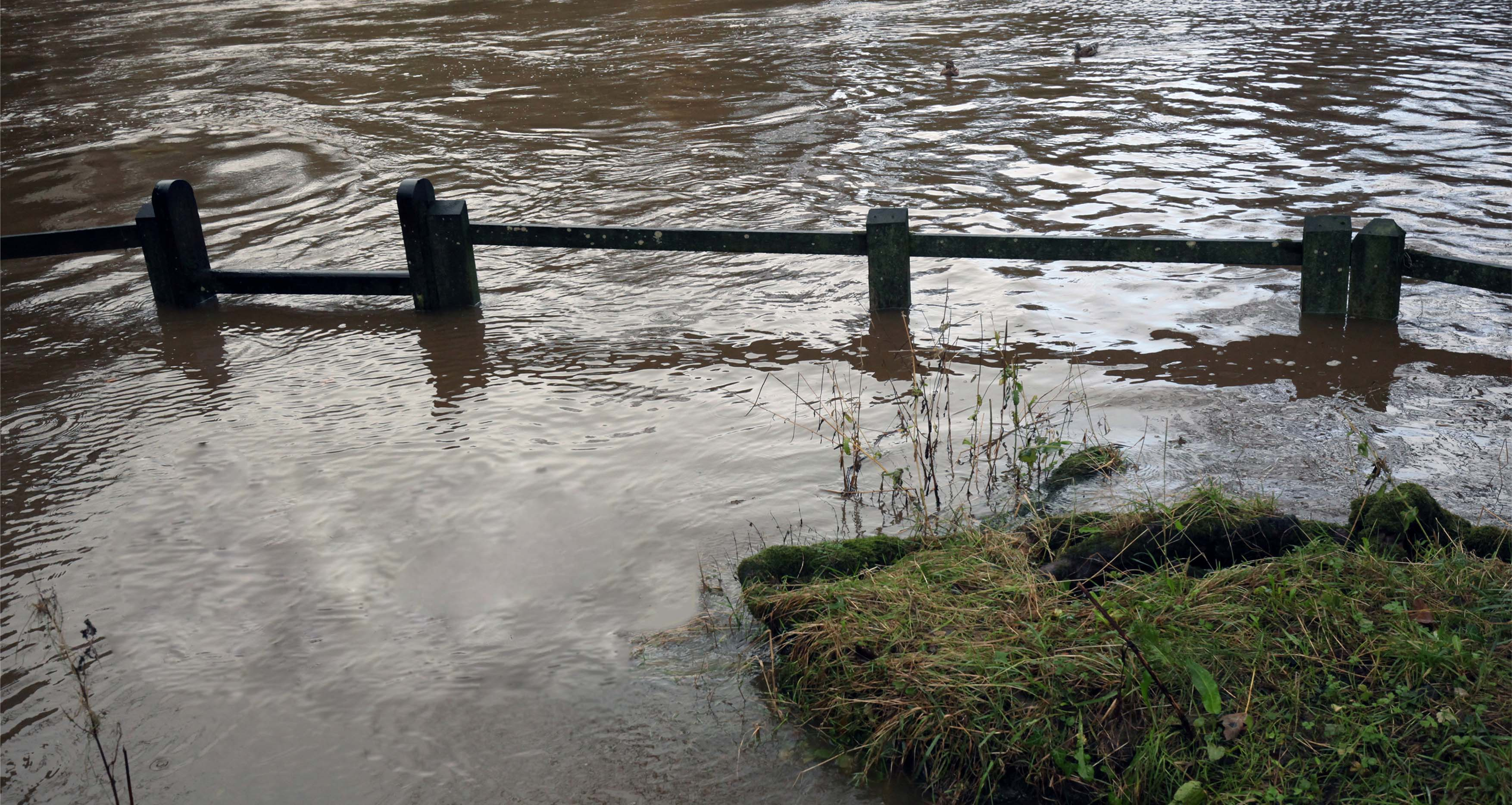 Flood waters in a field partially engulfing a fence