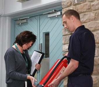 Business owner carrying out fire safety check with fire protection officer