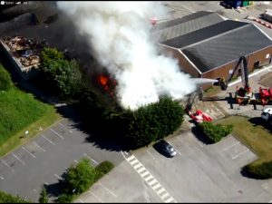 Aerial photo of a waste fire at an industrial site in Darwen. Lots of smoke is coming from the area and an aerial ladder platform is spraying a jet of water onto the flames