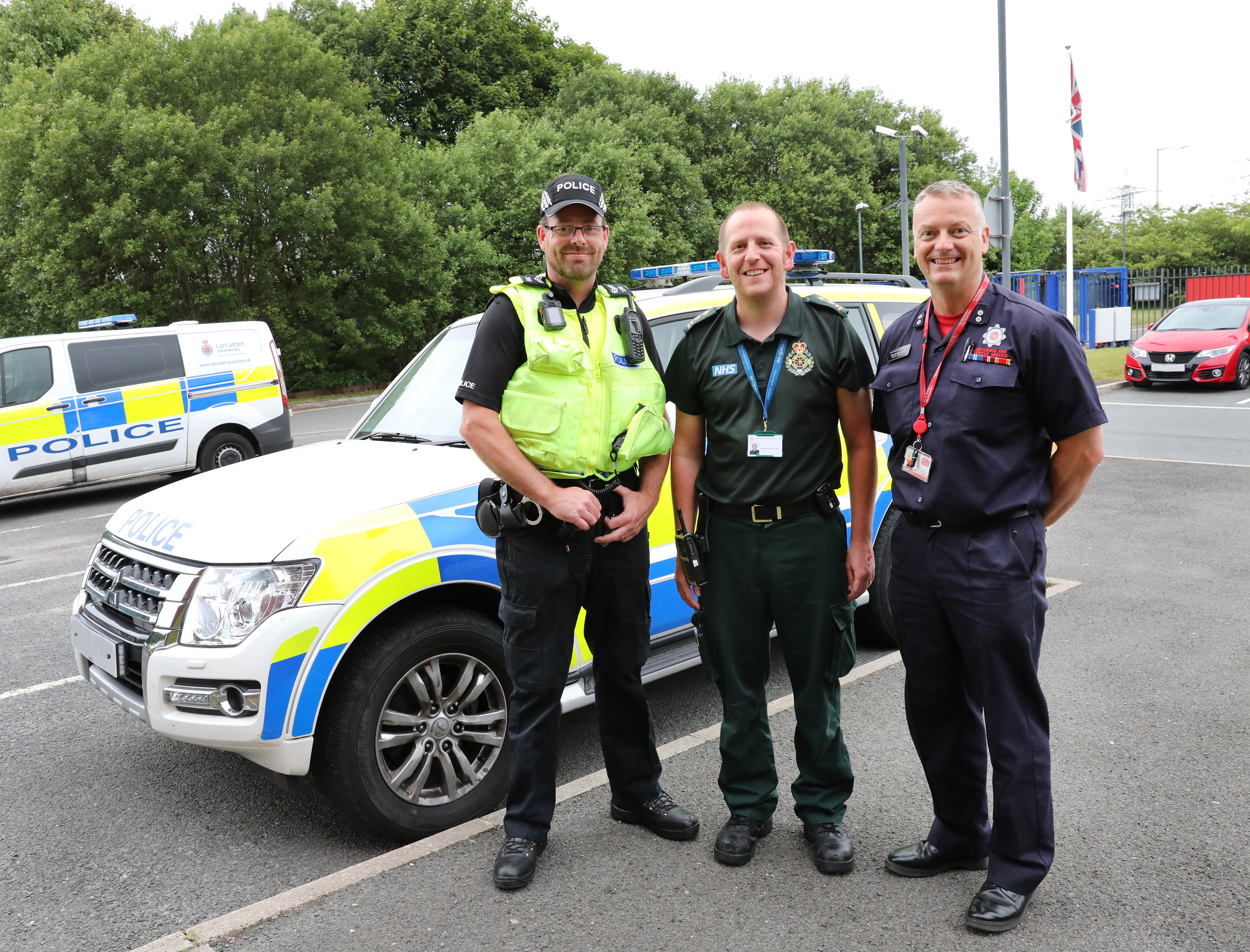 Three men stood next to a Police vehicle. One is a Police officer, one is a paramedic and one is a firefighter