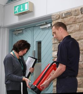 Fire Safety Officer and Business Owner checking a fire extinguisher