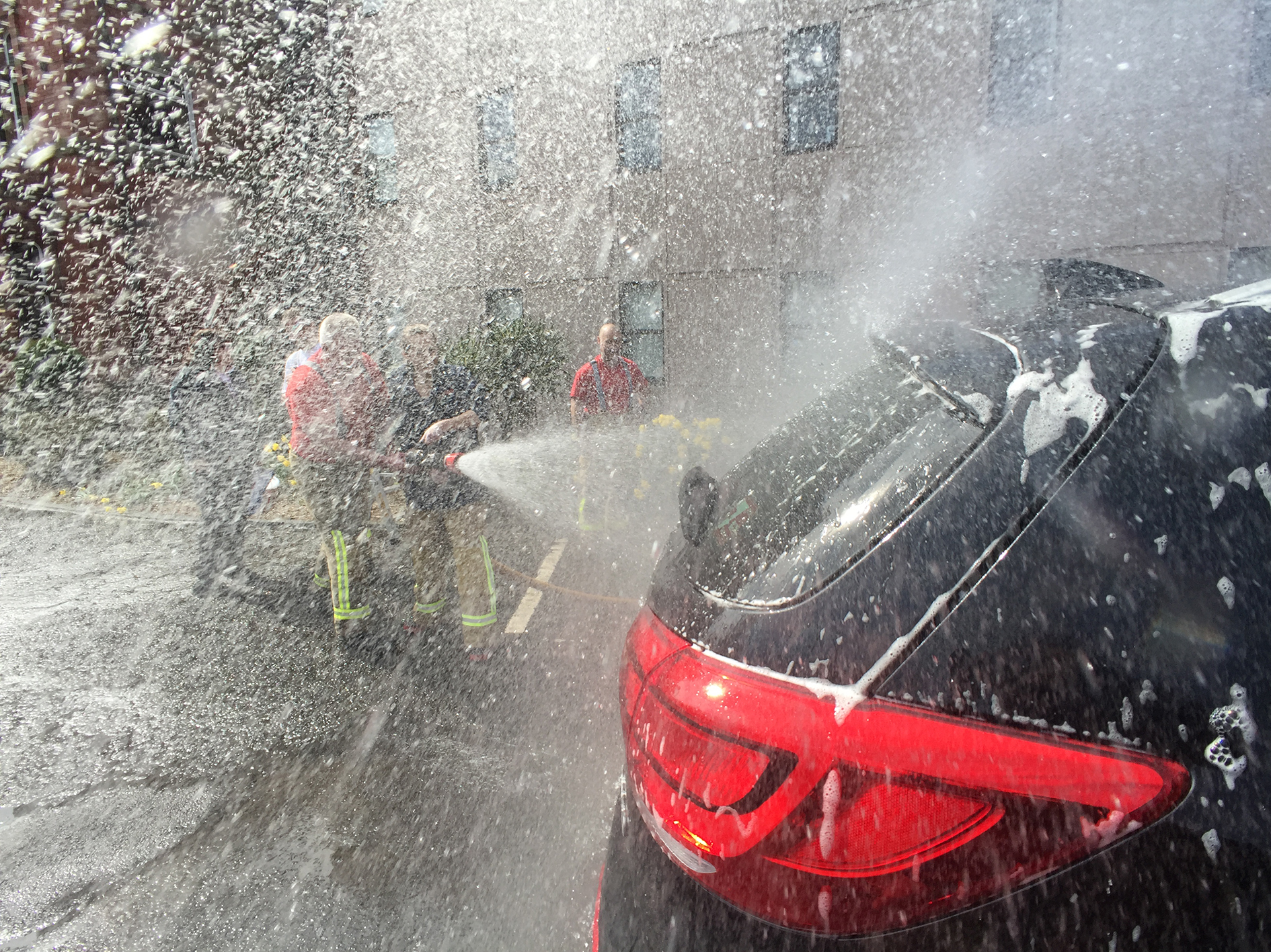 Firefighters spraying soap suds of the back of a car. Suds are flying everywhere.