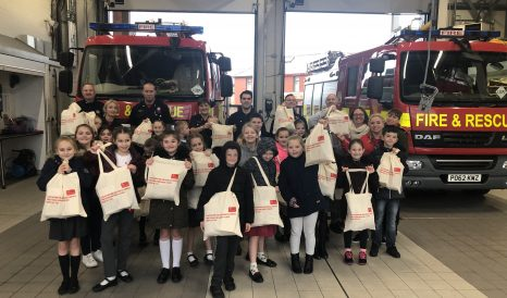 Flakefleet primary school children with firefighters and fire engines in the fire station