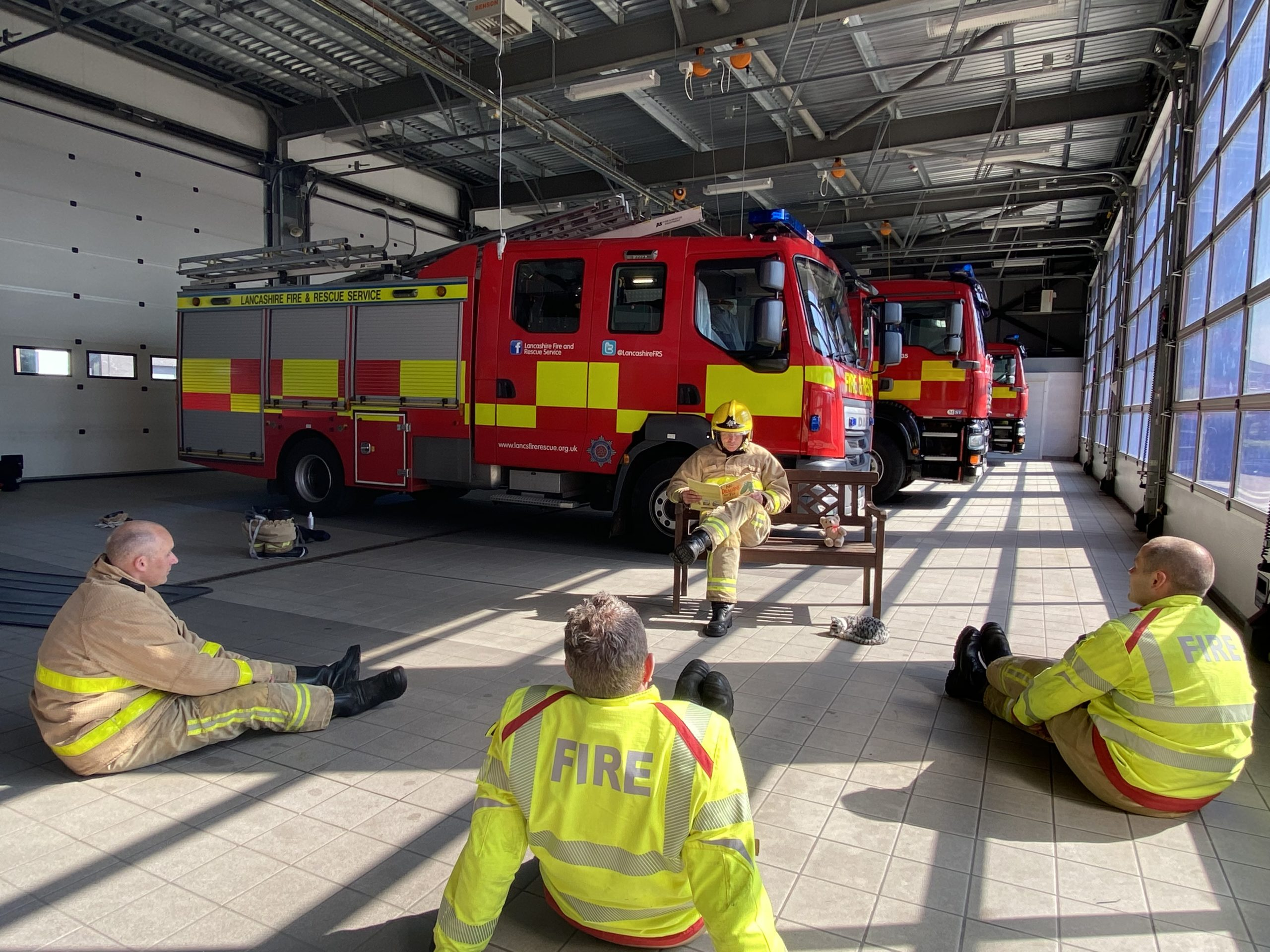 a firefighter hosts a storytime session with his crew at Burnley fire station