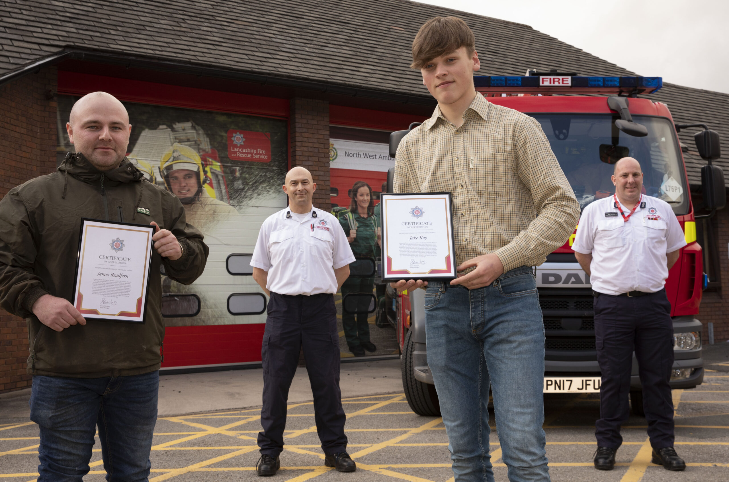 Presentation to James Readfern and Jake Kay in front of Darwen Fire Station and fire engine with Group Manager Wilson and Station Manager Harvey